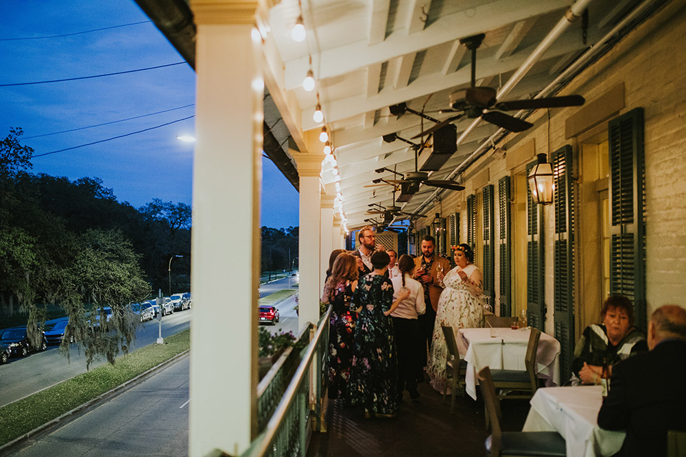 The wedding guests enjoy cocktails on the balcony at Ralph's on the Park overlooking New Orleans' historic City Park. Photo: Ashley Biltz