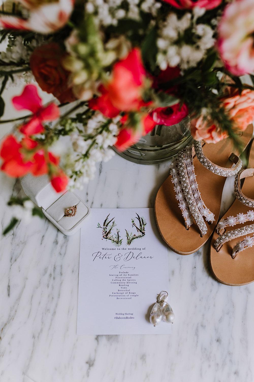 Wedding details including the wedding program, bridal bouquet, engagement ring, earrings and wedding shoes. Photo: Ashley Biltz