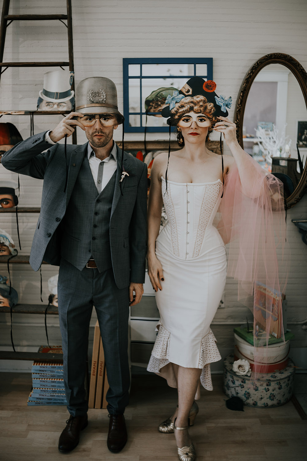Bride and groom pose with vintage-style masks from L. Delaney's Imaginarium