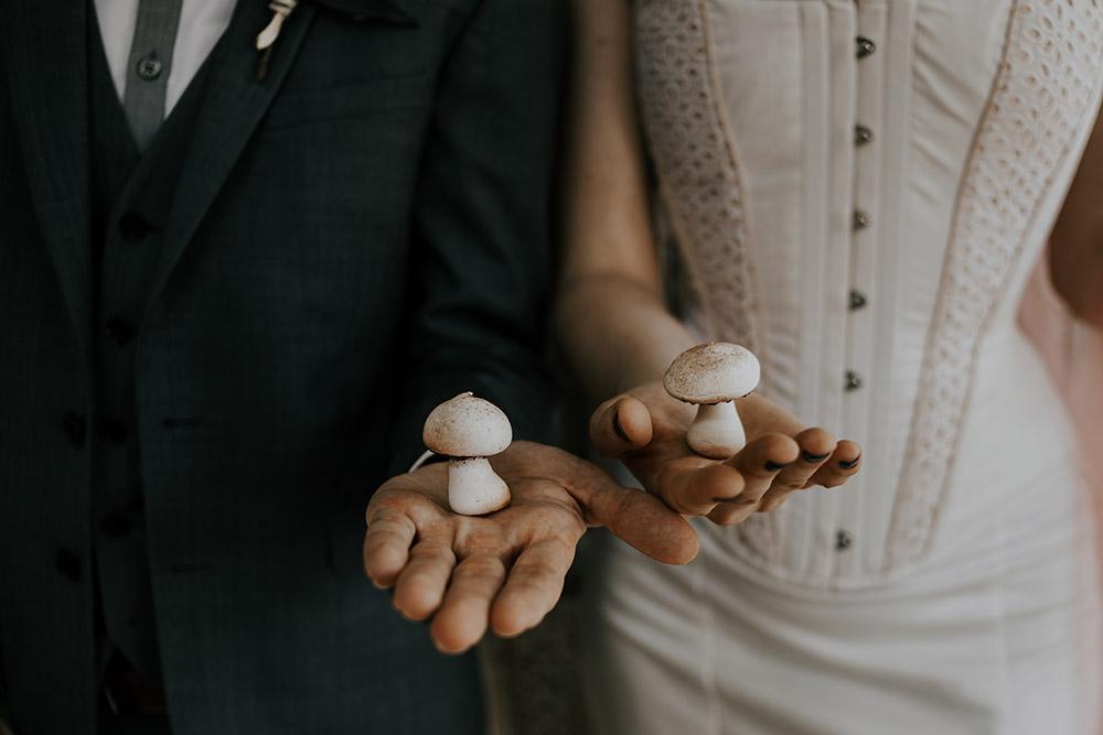 Bride and groom each hold a mushroom meringue