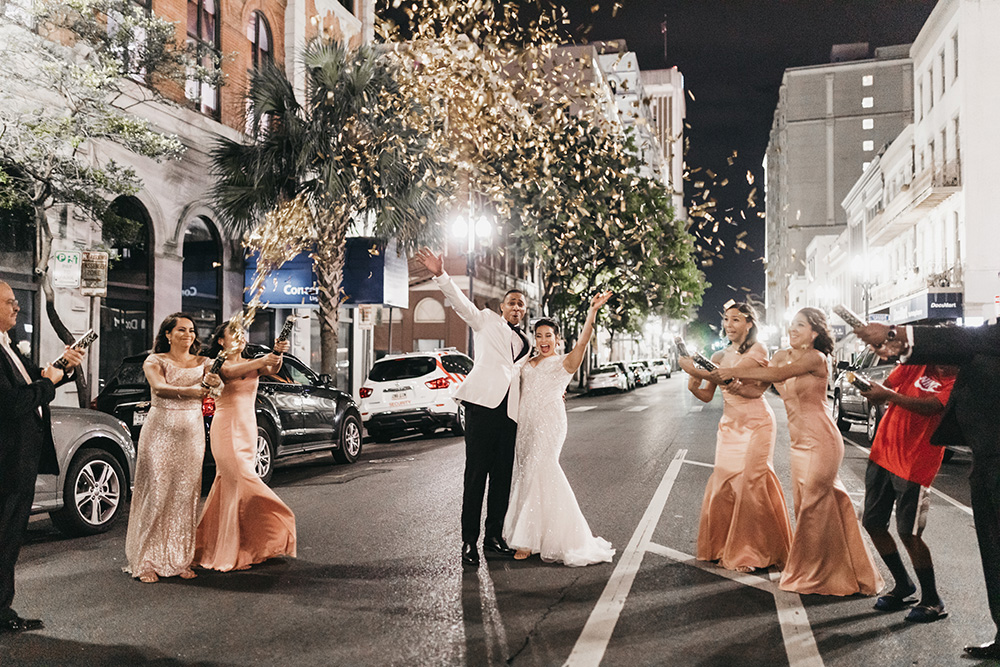 The wedding party celebrates in the street.