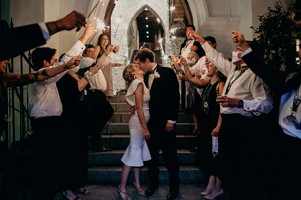 Ashley and Peter kiss as they exit Felicity Church while guests light the way with sparklers.