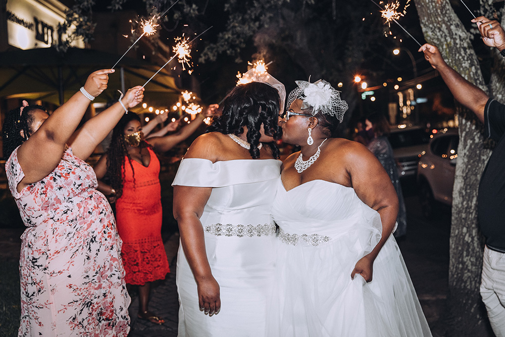 The brides kiss during their sparkler exit.