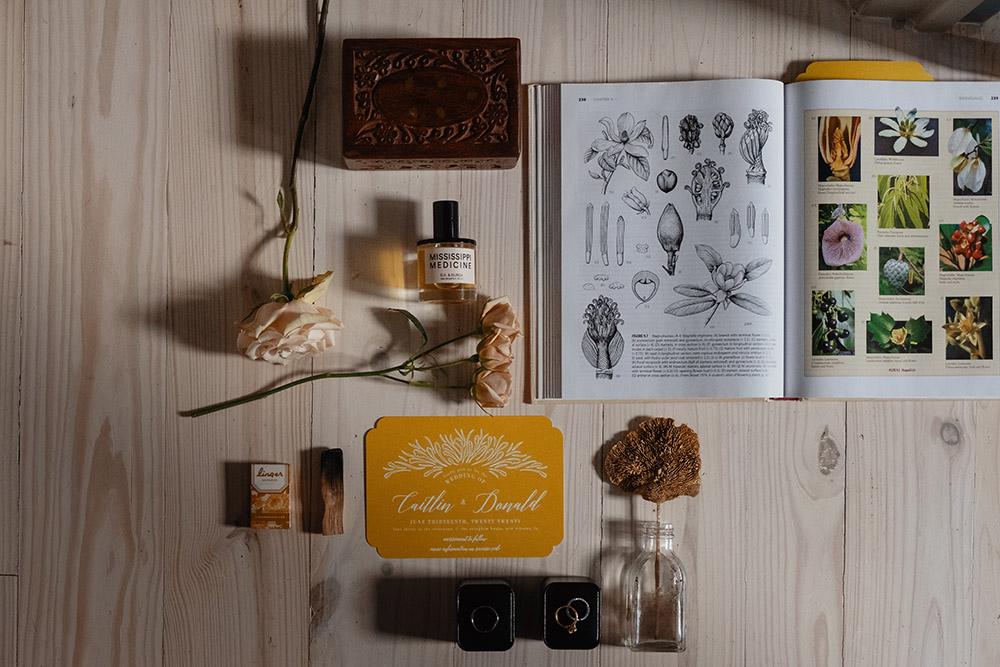 The wedding invitation, rings and a botany book flatlay. Photo: Dark Roux