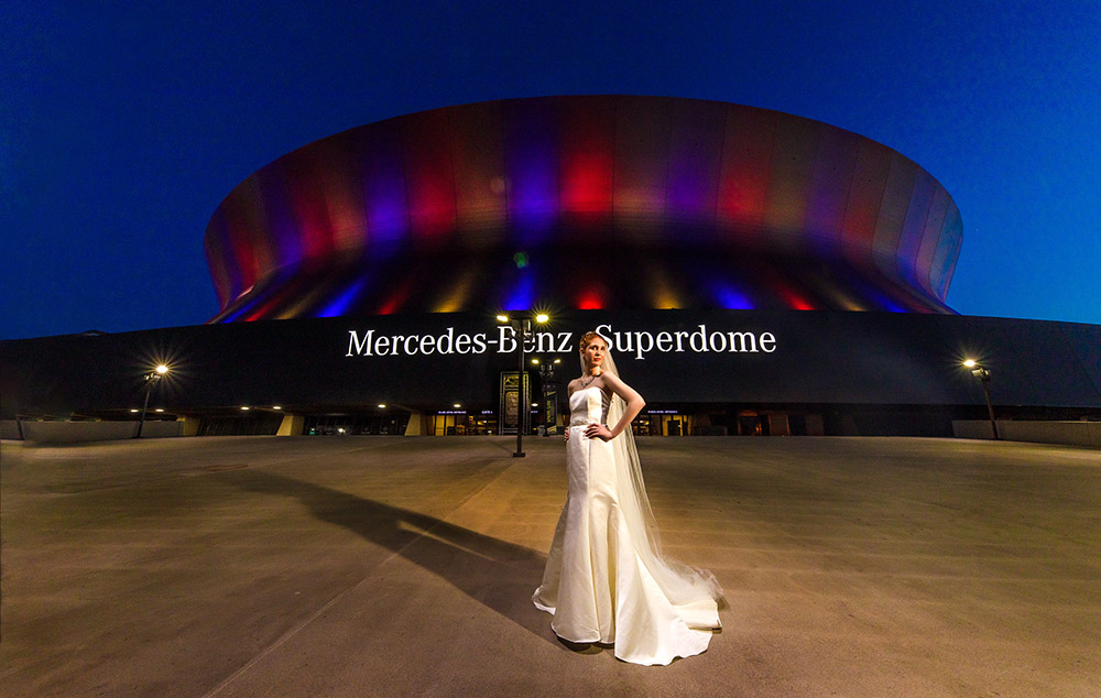 A bride poses in front of the Mercedes-Benz Superdome in New Orleans