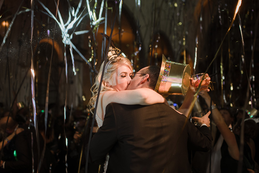 The newly weds kiss at midnight as streamers and confetti fall around them.
