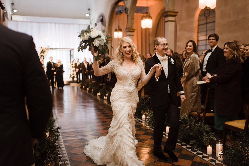Chelsea and Ross celebrate as they walk down the aisle.