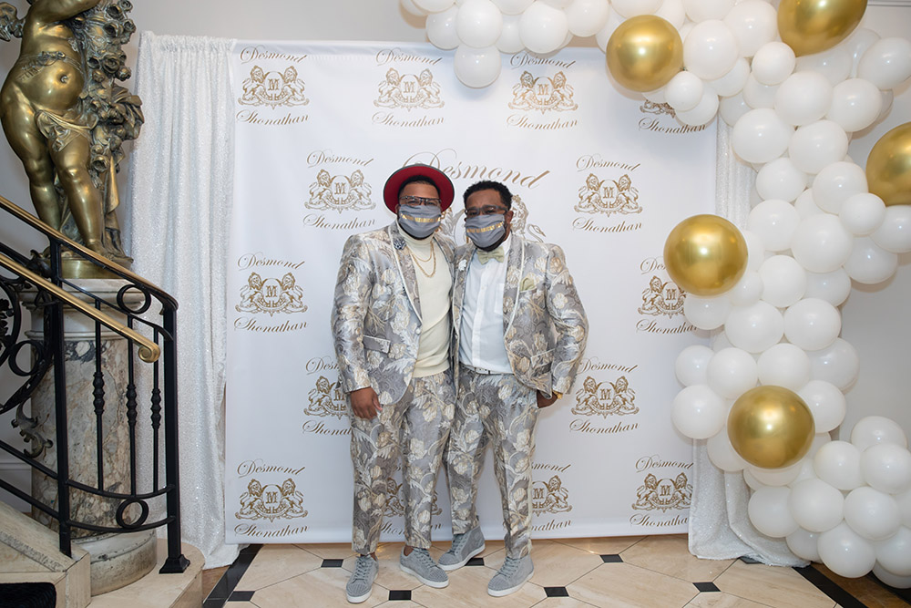 Shonathan and Desmond pose for photos in front of the custom designed logo wall and balloon installation at their engagement party.