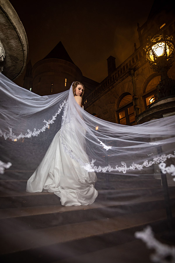 Dramatic veil photo of bride walking up stairs