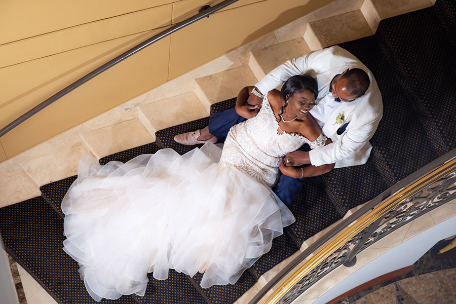 Bride and groom lounge on elegant staircase