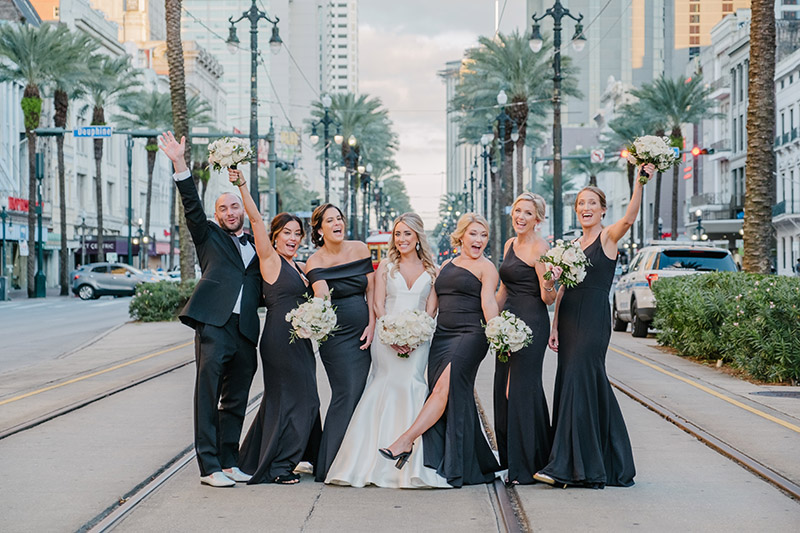 A bride and her bridesmaids pose on Canal Street in New Orleans | Photo: Studio Tran