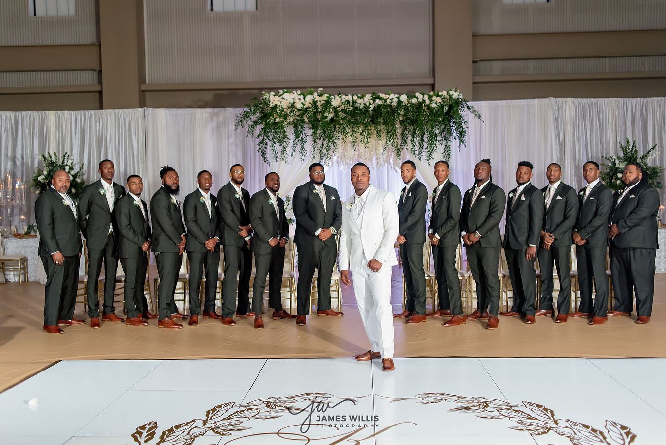 Groom in white tuxedos and groomsment in grey tuxedos from Tuxedos to Geaux