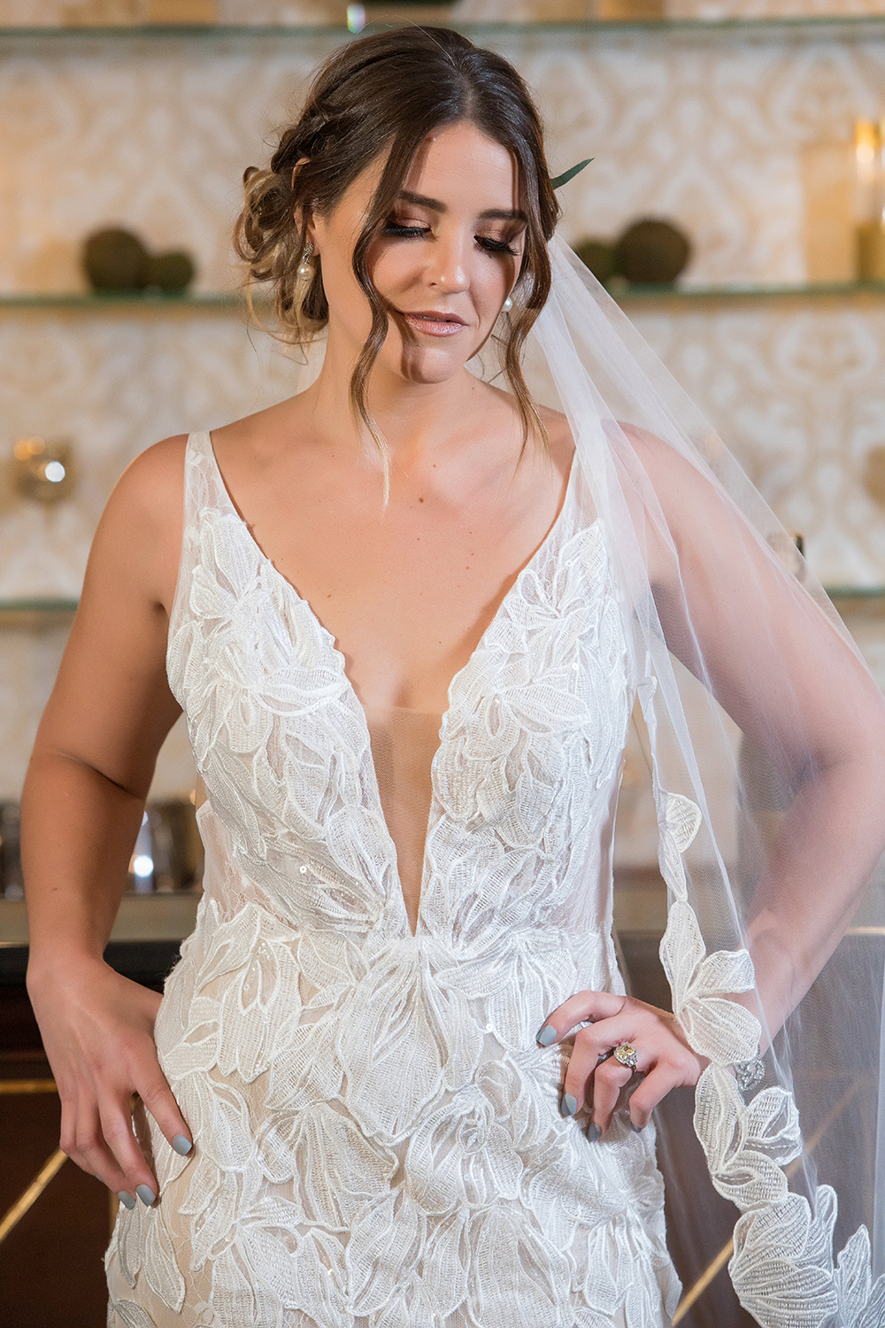 "Evie is wearing an ivory lace fit and flare gown with deep V-plunge and dramatic cascading train available at MaeMe The Bridal Boutique. Matching veil available. For her ""Something Blue"" Passport Polish's short length Ready Made Press-ons in one of their newest colors, Iceland."