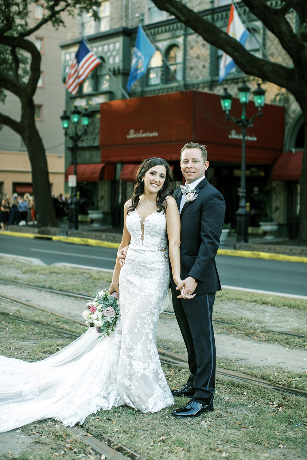A bride and groom pose on the Neutral Ground outside the Pontchartrain Hotel