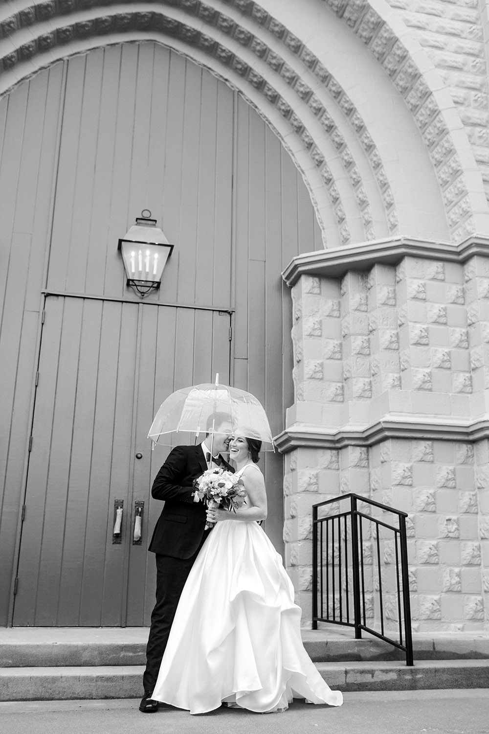 Black and white photo of a bride and groom under an umbrella