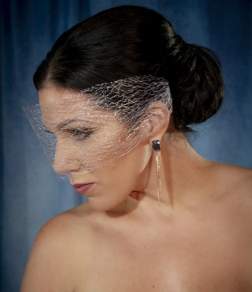 A silver net birdcage veil and blue rhinestone drop earrings with rose gold waterfall tassel complete her look.