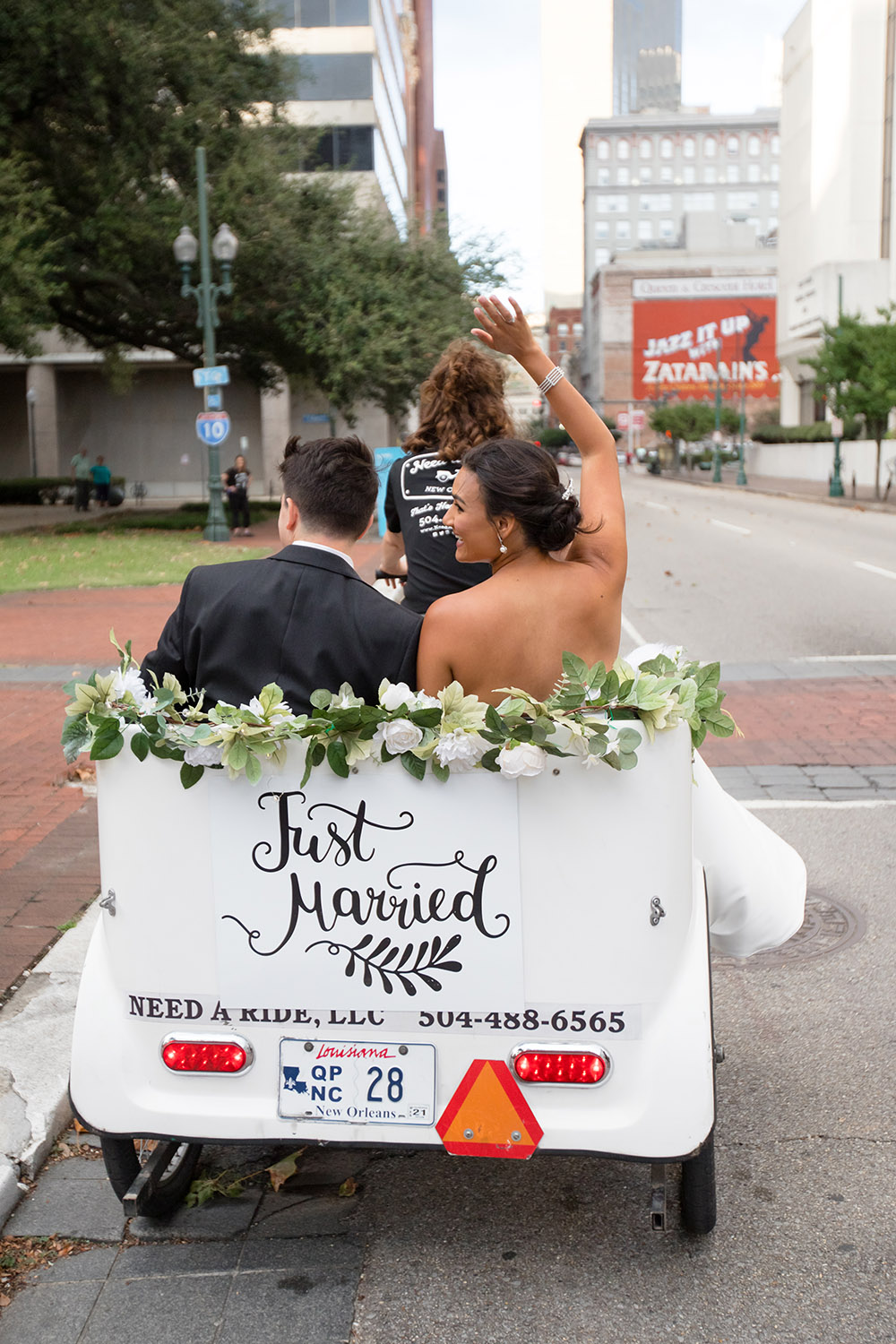 The bride and groom ride in a pedicab to their reception