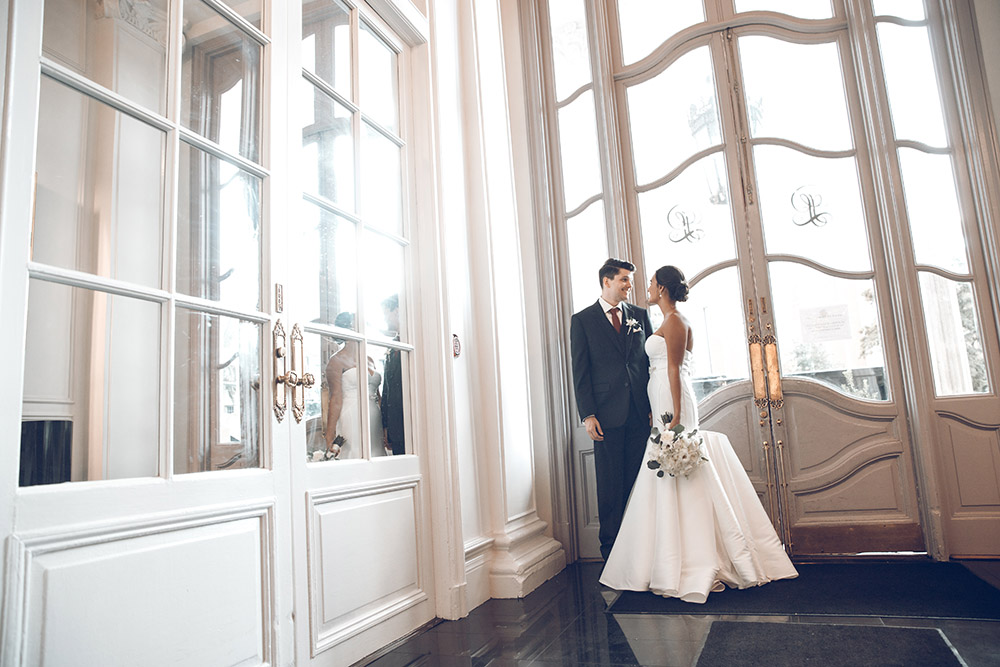 The bride and groom pose in the lobby of Le Pavillon Hotel