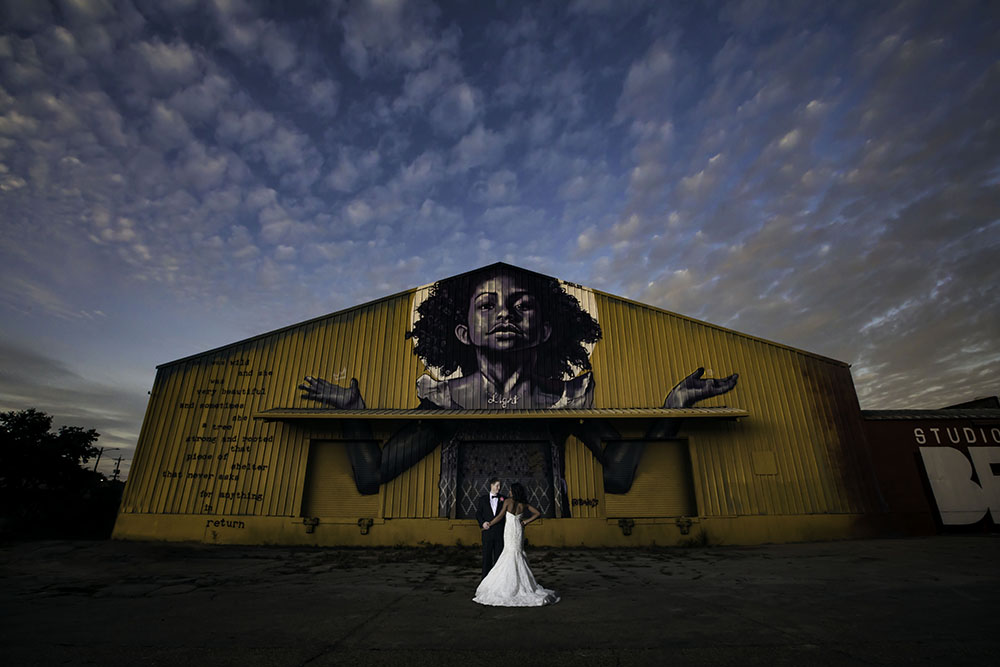 Bride and Groom posing in front of Bywater warehouse with mural by Brandon Bmike Odums | Brian Jarreau Photography