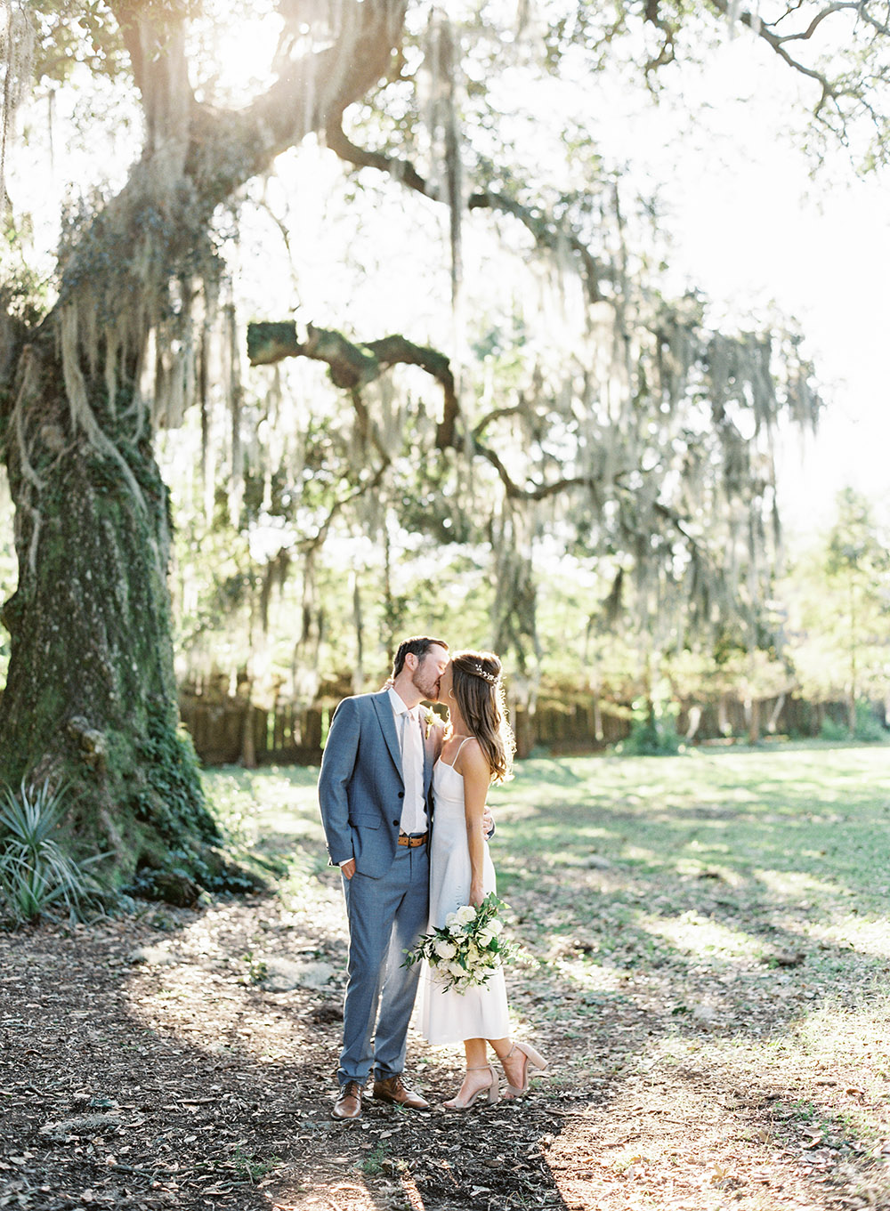Newlyweds kiss at the Tree of Life in Audubon Park by Peony Photography