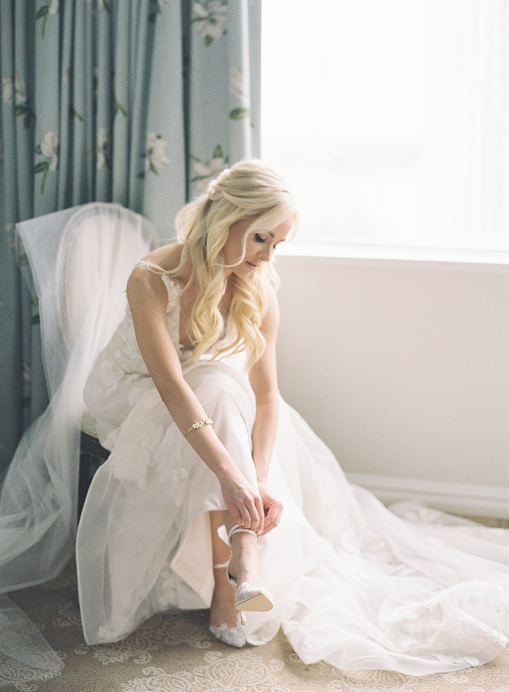 Bride adjusts her shoe by Peony Photography