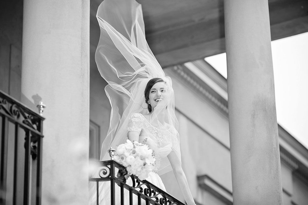 Black and white photo of a bride with veil blowing by Eau Claire Photographics
