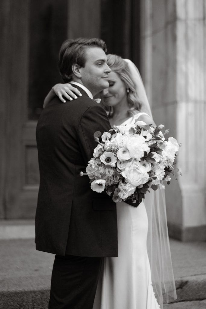 Black and white photograph of a bride and groom embracing by Eau Claire Photographics