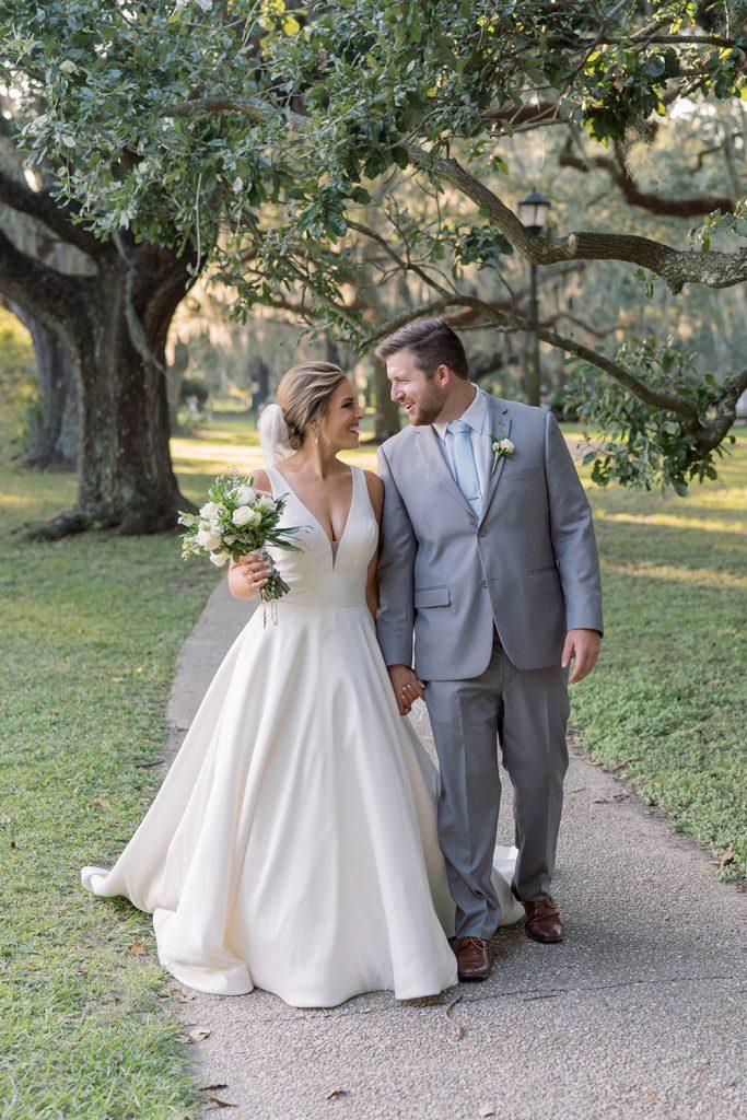 Bride and groom walk in Audubon Park by Eau Claire Photographics