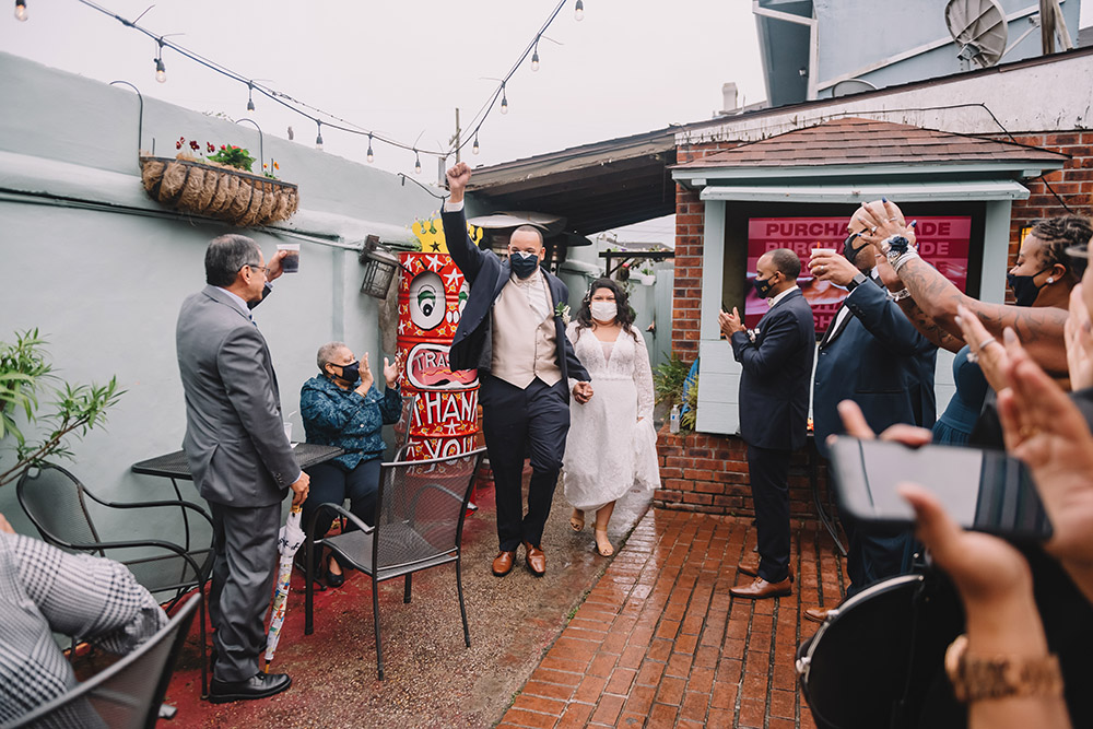 Ian and Mari enter the courtyard of Down the Hatch in New Orleans for their wedding reception. Photo by Rare Sighting Photography