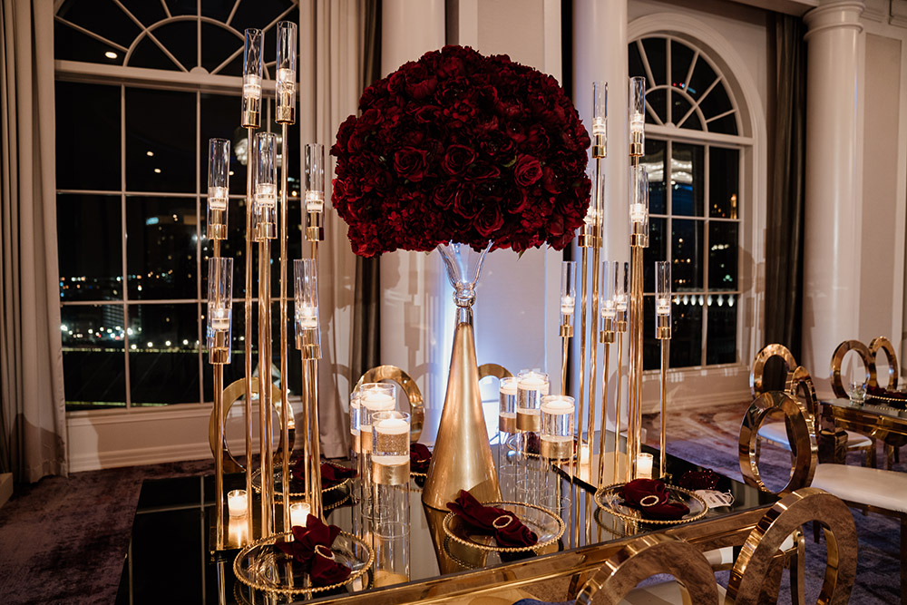 Close up of the gold and glass tables with candles and burgundy rose centerpieces. Photo by Audie Jackson