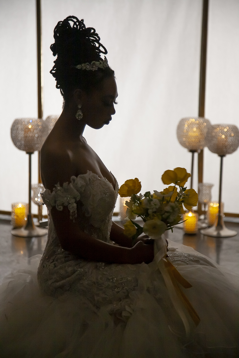 Silhouette of a bride gazing at her bouquet. Photo by Jessica Burke