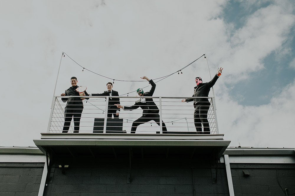 Chris and the groomsmen have fun on the rooftop of their AirBnB before the wedding. Photo: Sara Ann Green Photography
