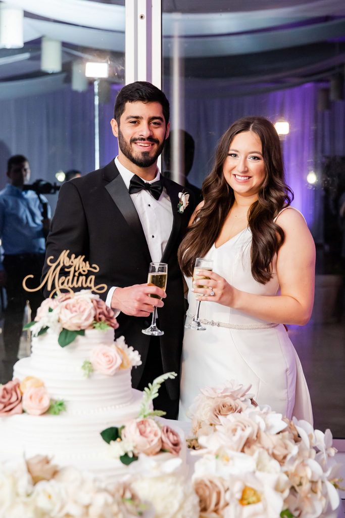 Kaylin and Julius toast by their wedding cake.