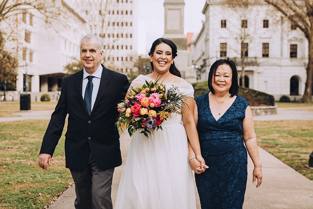"""Isabella and her parents walk down the """"aisle"""" at Lafayette Square."""