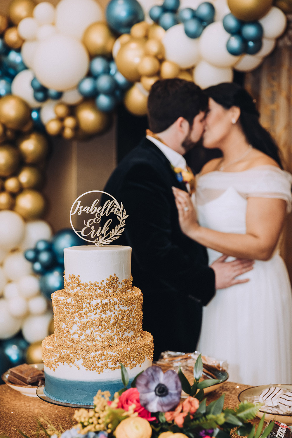 The bride and groom kiss by the wedding cake