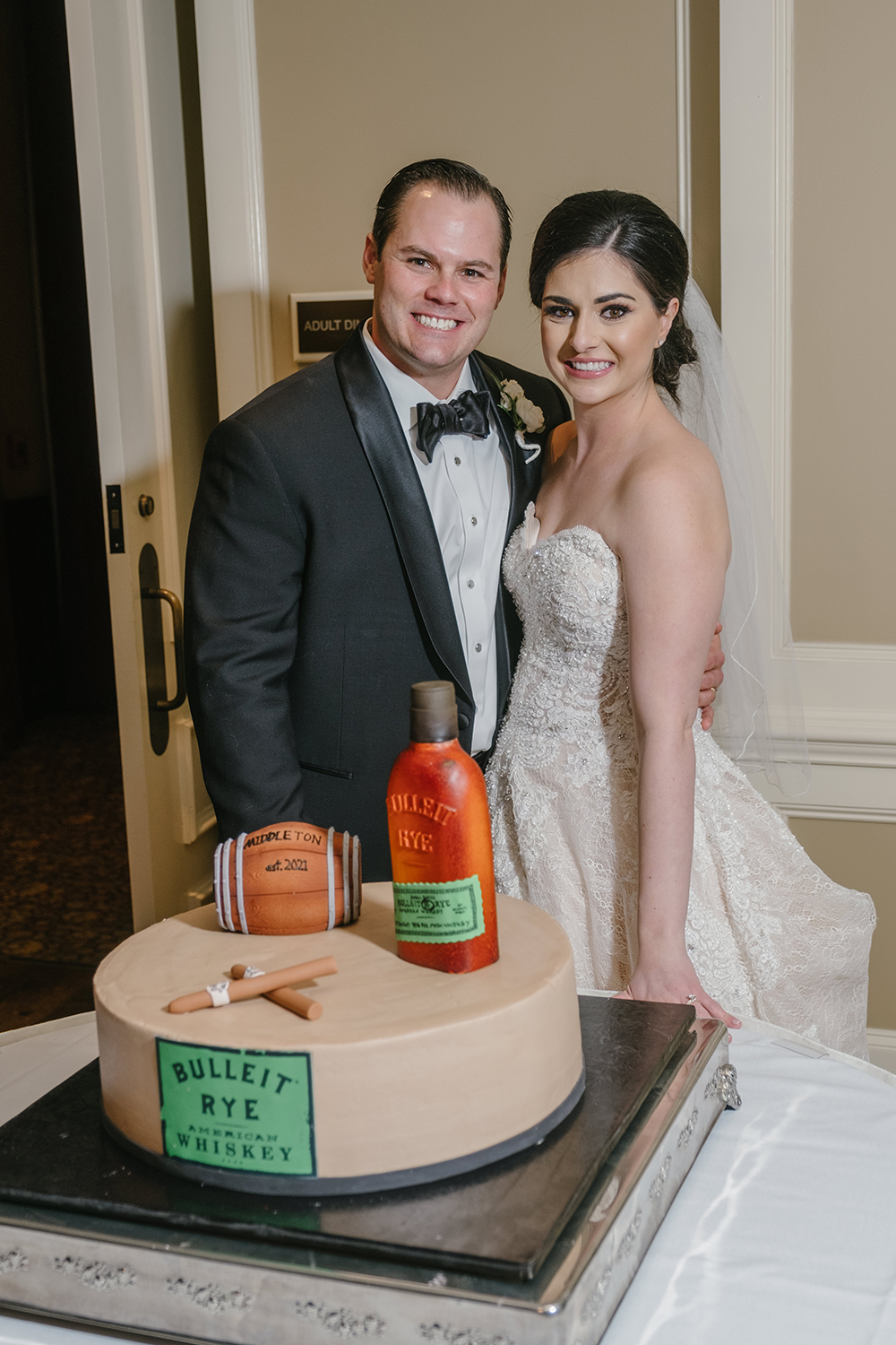 The bride and groom pose with the groom's cake