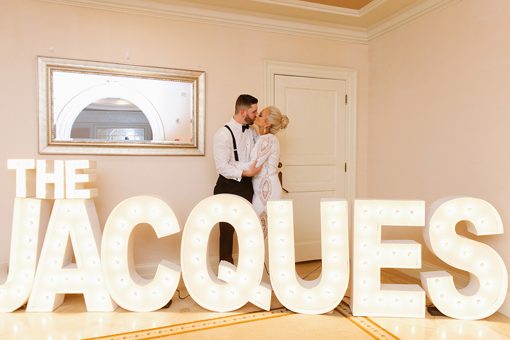 The bride and groom pose with marquee letters spelling their name