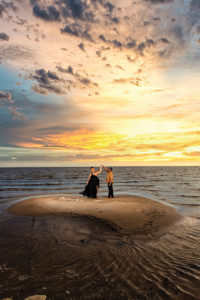 Beach engagement photo at sunset by Amin Russell Photography