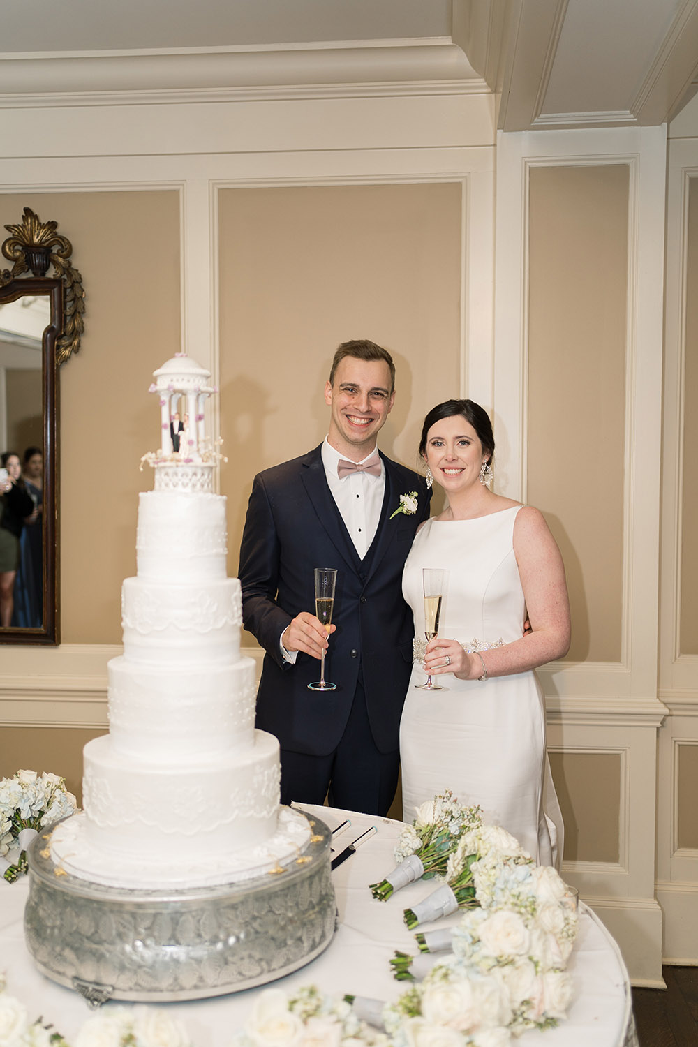 The newly weds toast by their wedding cake.