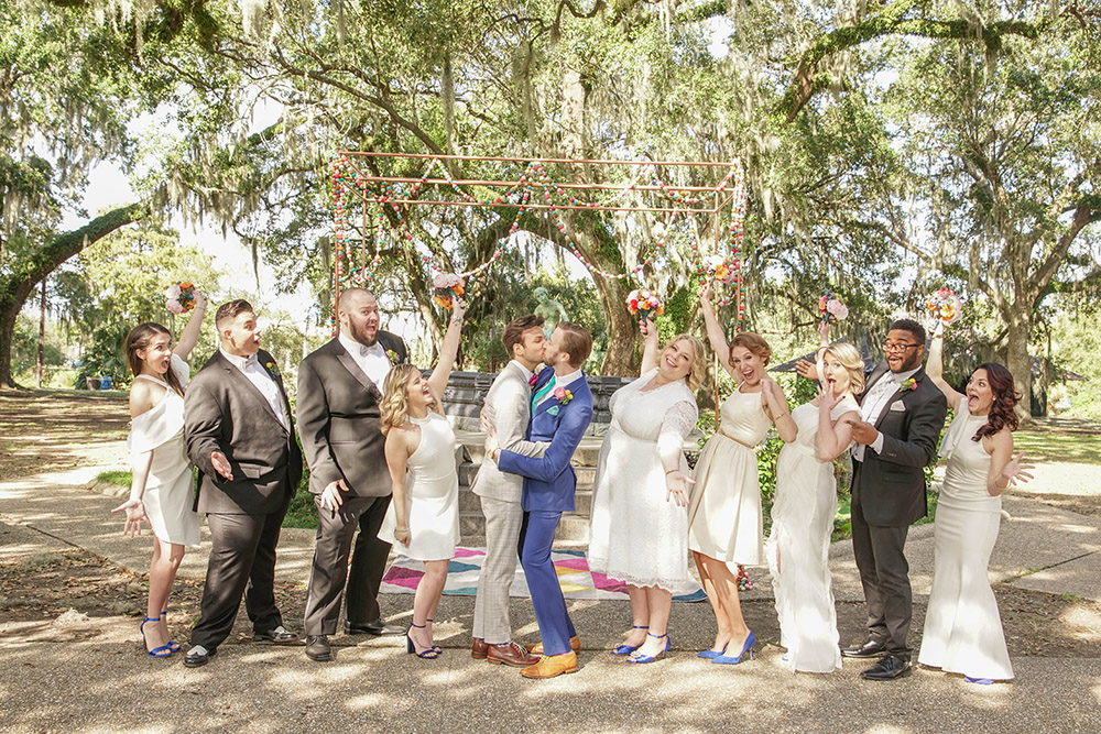 the wedding party celebrates with the grooms