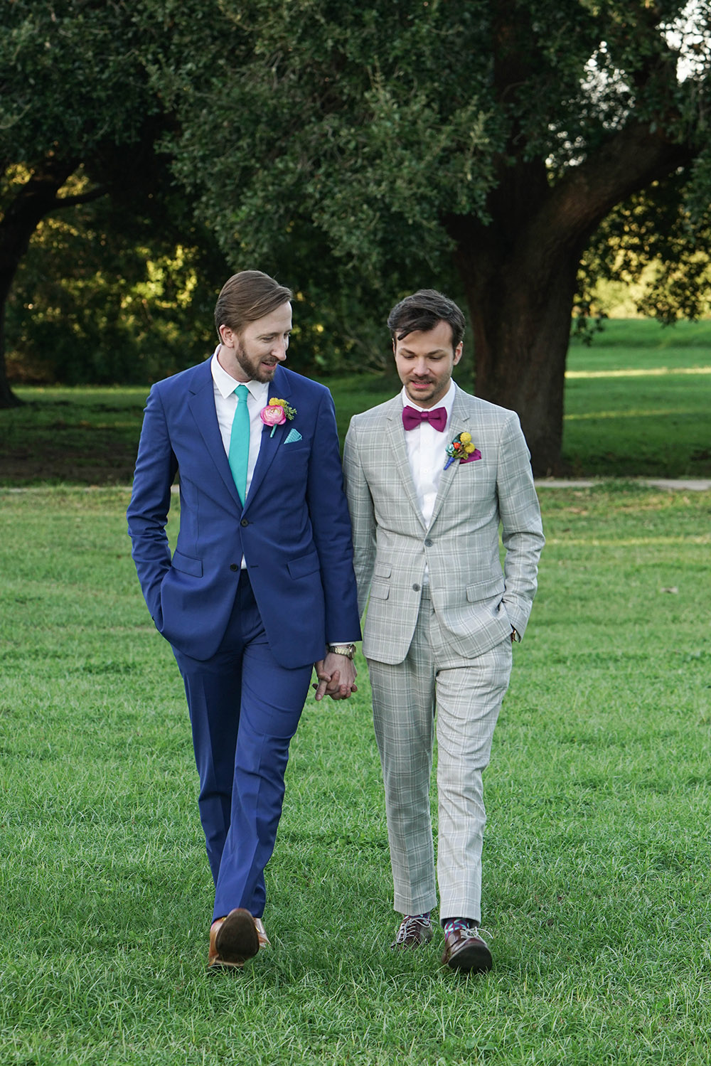 the grooms walk through New Orleans City Park holding hands