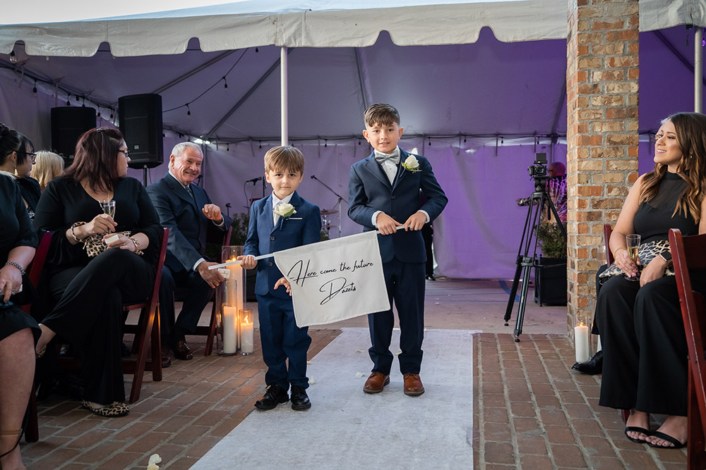 the ring bearers carry a sign announcing the brides
