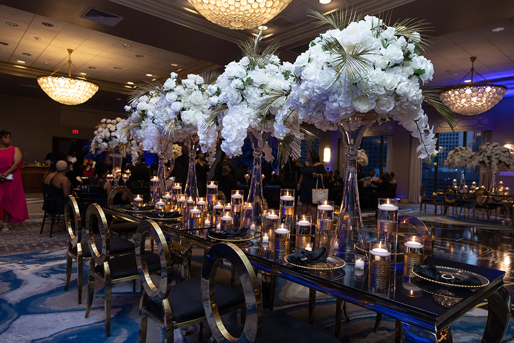 gold wedding reception table with white floral arrangements