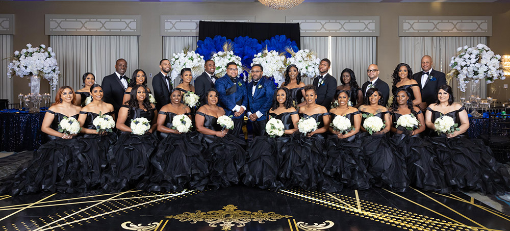 the wedding party in black and grooms in blue