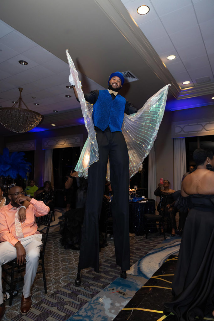 stilt walker with LED wings at the wedding reception