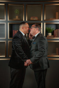 the grooms lean in for a kiss
