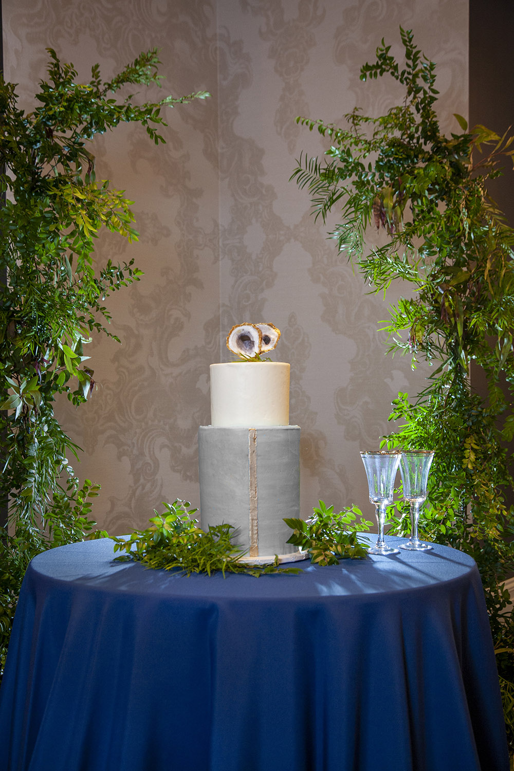 2 tier ivory and grey wedding cake with gold leaf and gold oyster cake topper