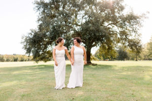 the brides hold hands and walk on the grounds of The Barn at Sarah Bella in Picauyne. MS