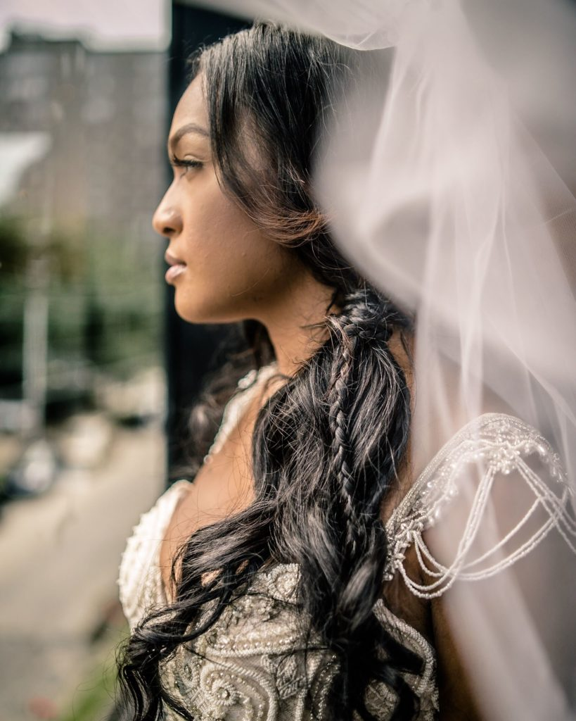 Bride looking out a window XXI Facets Photography