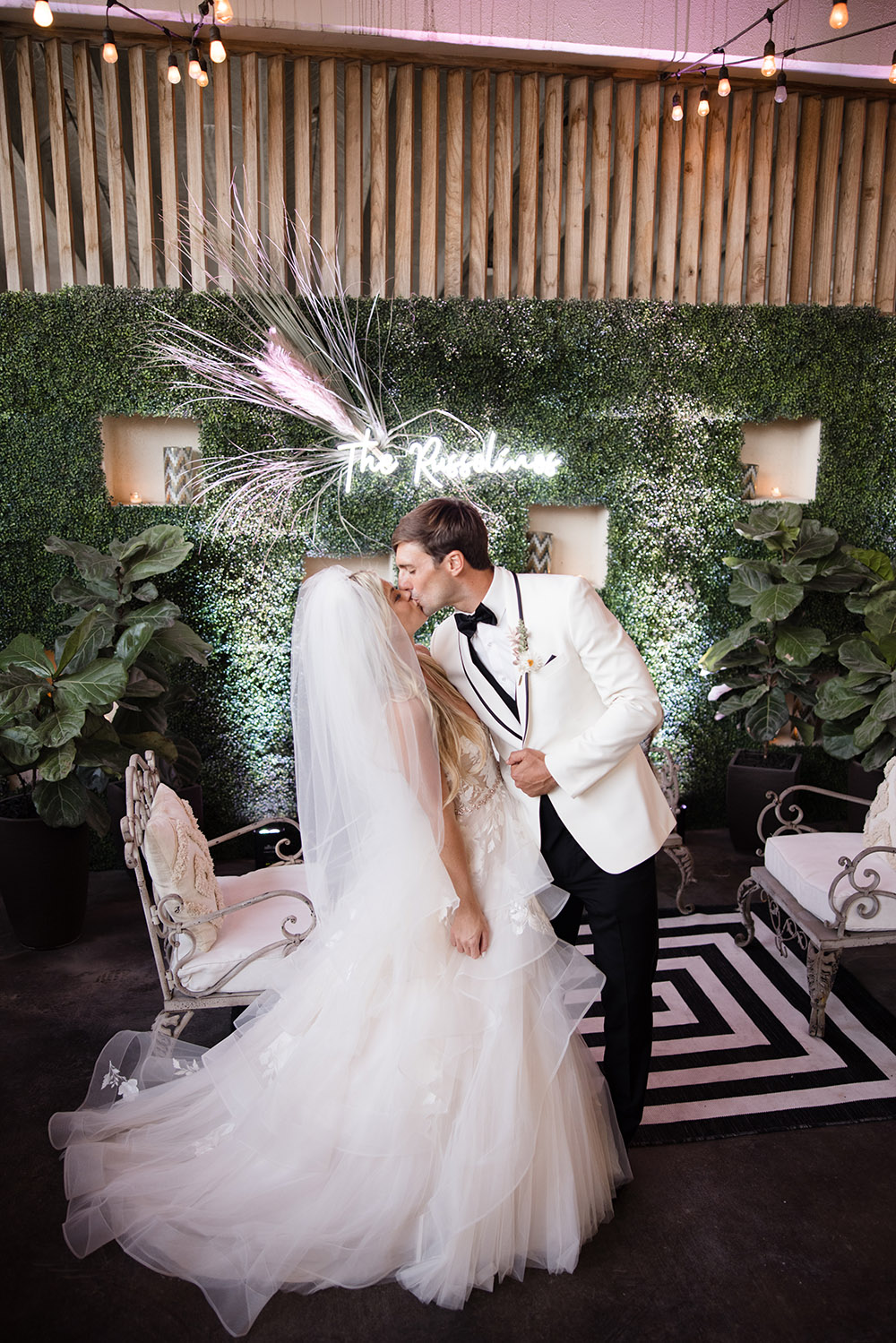 bride and groom with neon wedding sign